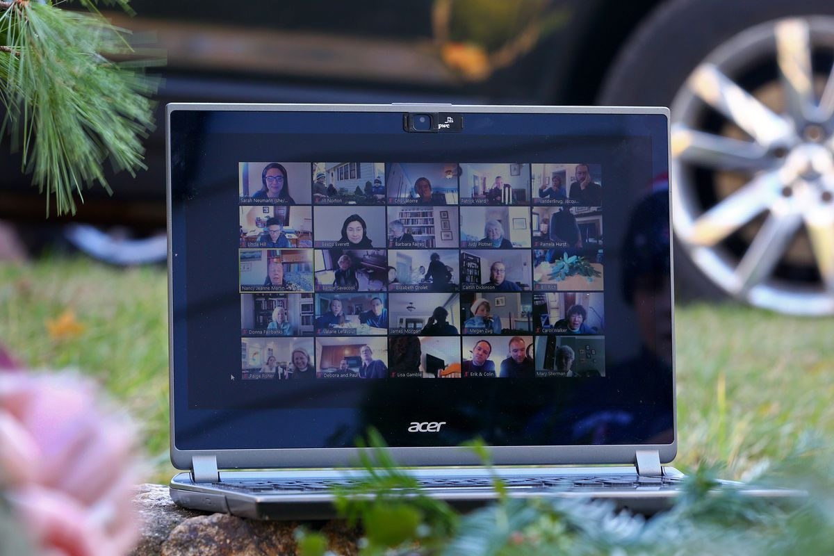 An open laptop sitting on a lawn and displaying a Zoom call with 20 participants.