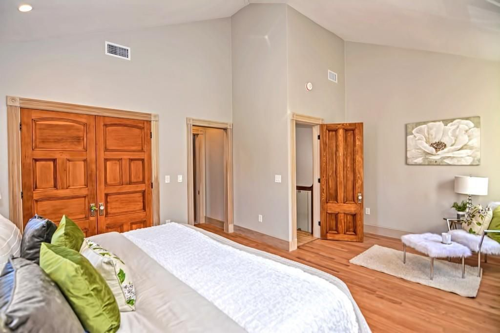 A bedroom with a bed and closed double doors, with the door to the bedroom open.