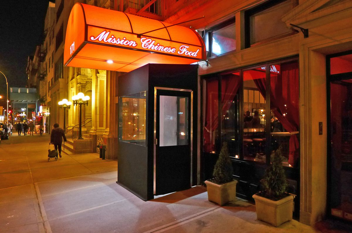The exterior of Mission Chinese by night, with a red awning glowing.