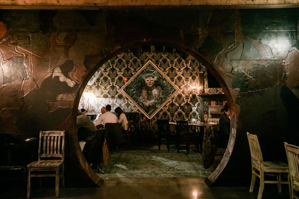 Customers sit in a dining room with weird black and gold wallpaper and a painting of a woman in a white bird-like masquerade mask. They're framed by a rounded doorway.