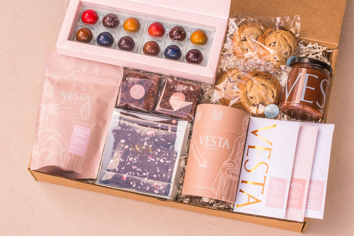 Several sweets including chocolate bars, bon bons, hot chocolate tins, all placed in a brown box