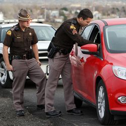 Utah Highway Patrol Sgt. Jacob Cox, right, and trooper Carlos Holley stop a motorist for texting while driving on Thursday, Dec. 13, 2012.
