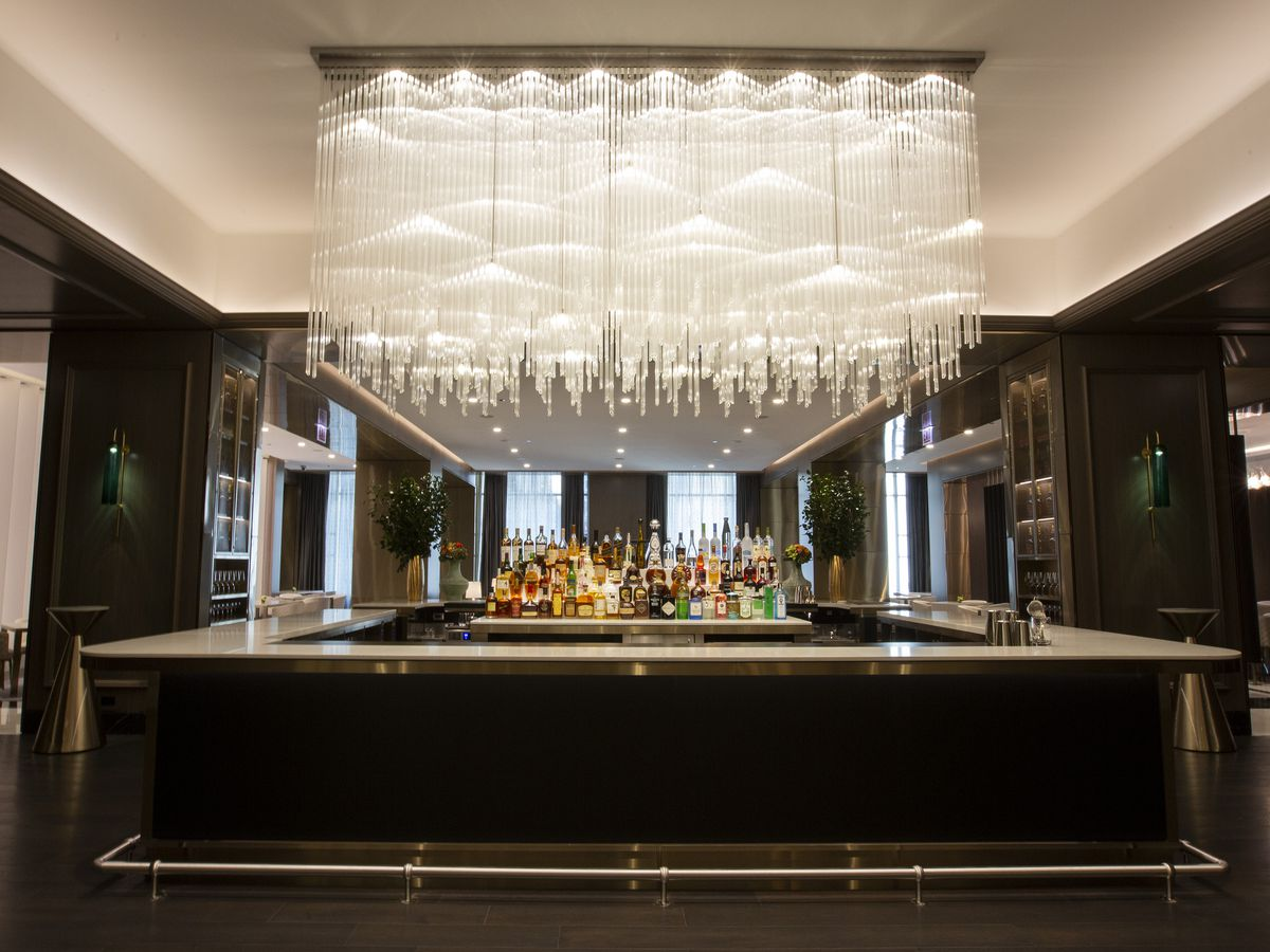A square black bar with a large modern chandelier hanging overhead.