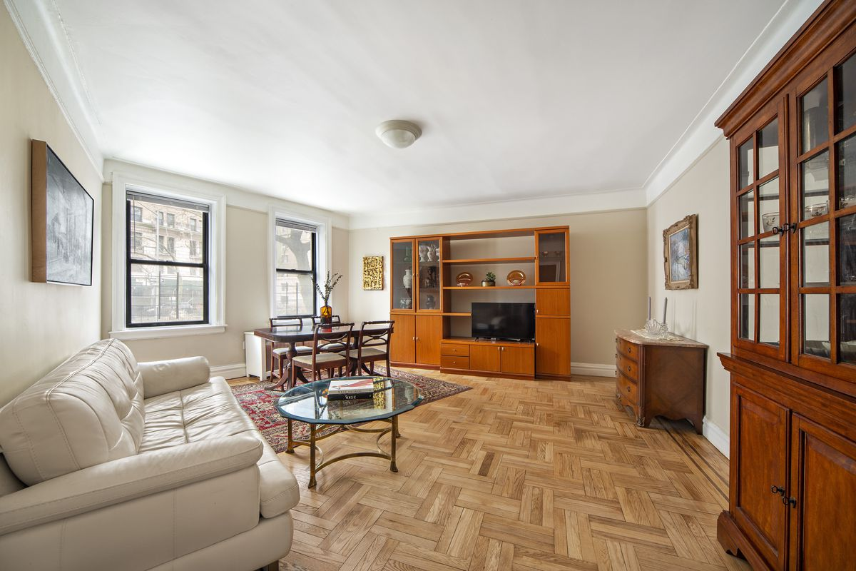 A living area with hardwood floors, beige walls, crown and base moldings, a beige leather couch, and a round coffee table.