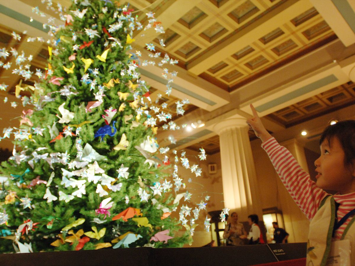 A child looks up at the American Museum of Natural History holiday tree. The tree is decorated with origami animals.