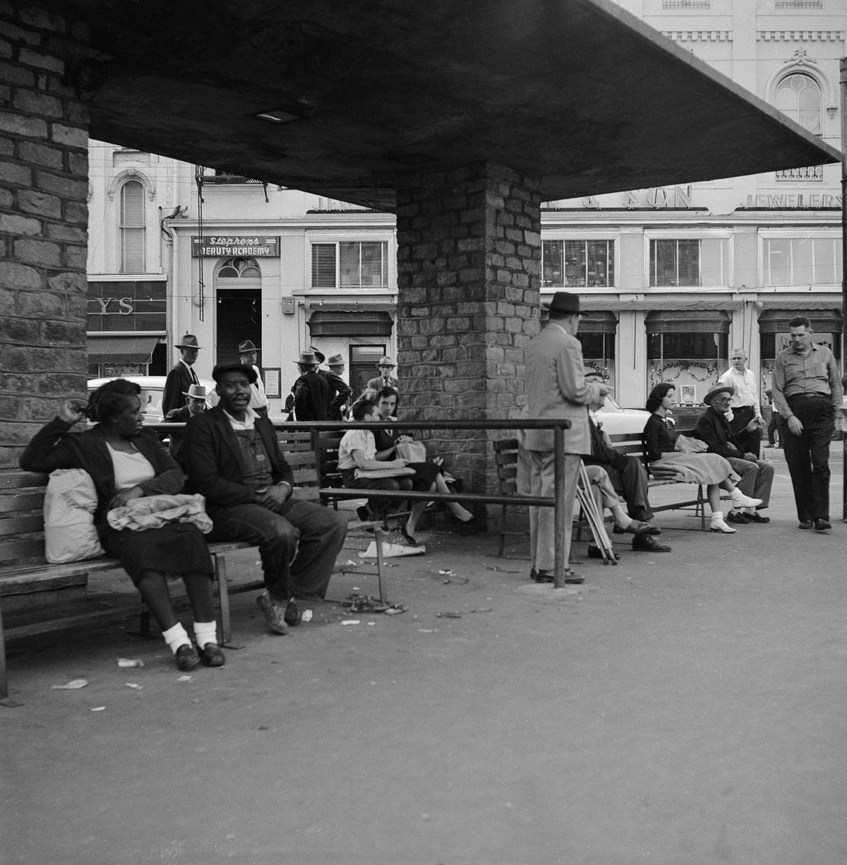 A Black man and woman talk on a bench that's separate from other white people by a dividing barrier.