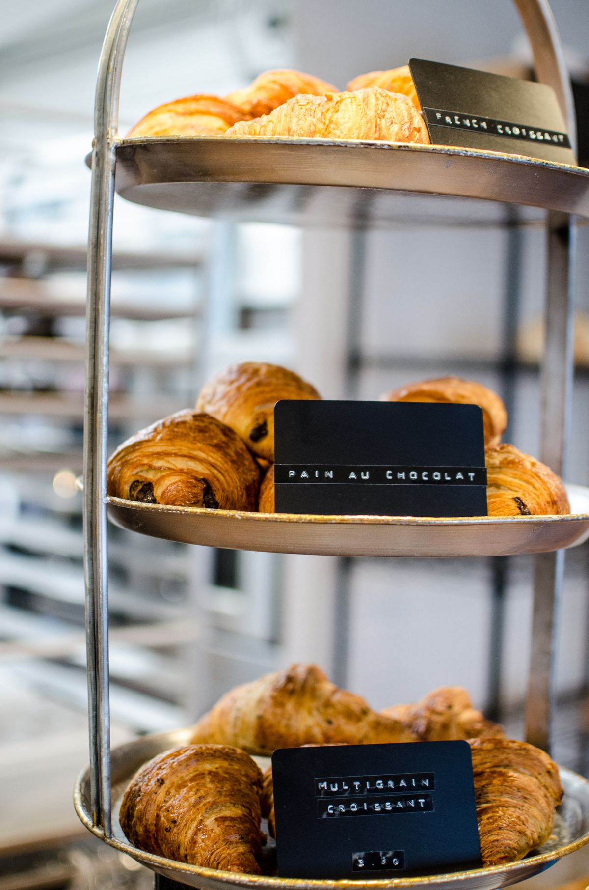 Multigrain croissants, pain au chocolat, and traditional croissants sit on a three-tiered set of metal plates.