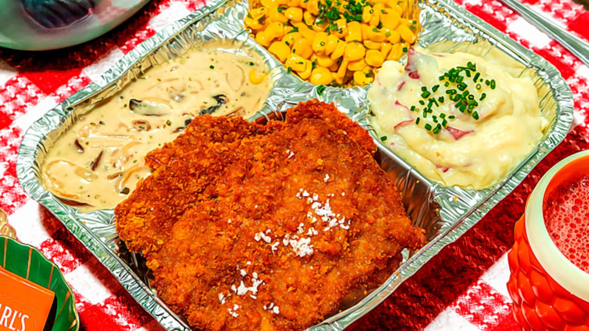 An old-school aluminum TV dinner tray with four compartments: panko breaded pork cutlet, mushroom and onion gravy, corn, and mashed potatoes.