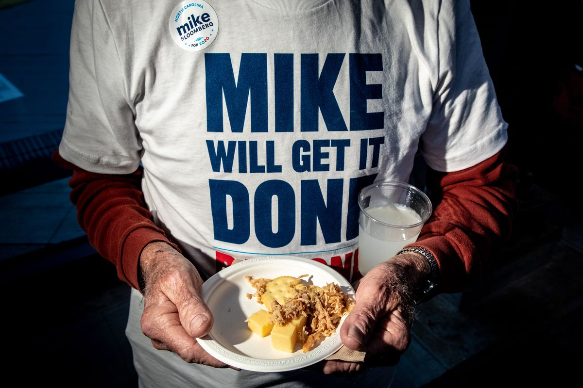 "A person wearing a ""Mike Will Get It Done"" t-shirt holds a plate of food and a plastic cup of liquid."