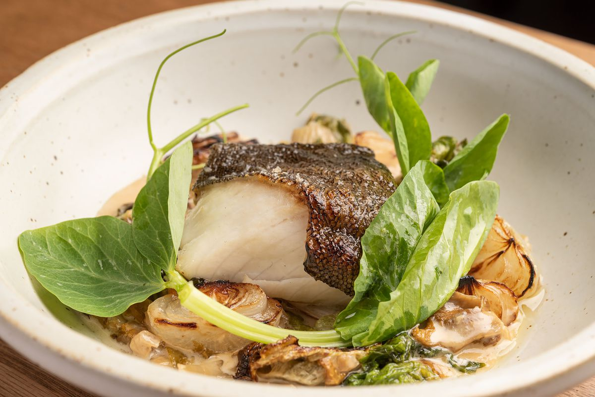 Crispy skinned black cod with vegetables and onions.