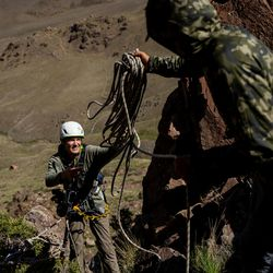 Hawkwatch International research associate Dustin Maloney, left, and field biologist Jayden Skelly prepare rigging so Maloney can enter two golden eagle nests on Antelope Island on Wednesday, May 19, 2021.