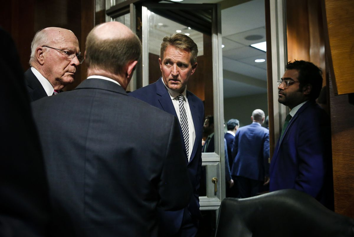 Sen. Jeff Flake (R-AZ) confers with Senators Patrick Leahy (D-VT) and Chris Coons (D-DE) while leaving the Senate Judiciary Committee meeting on September 28, 2018.