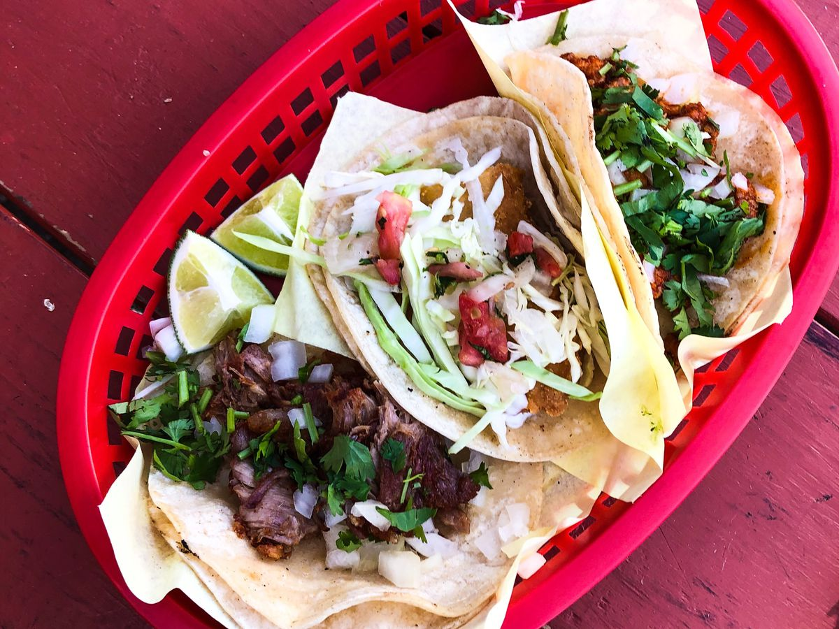 Three tacos sit in a red basket at El Coyote in St. Johns