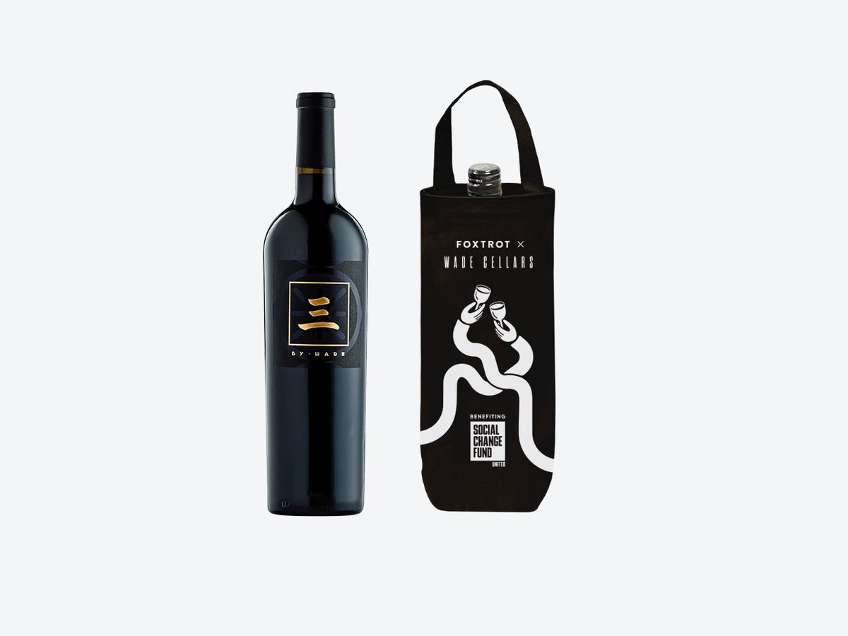 A black bottle of wine next to a wine tote.