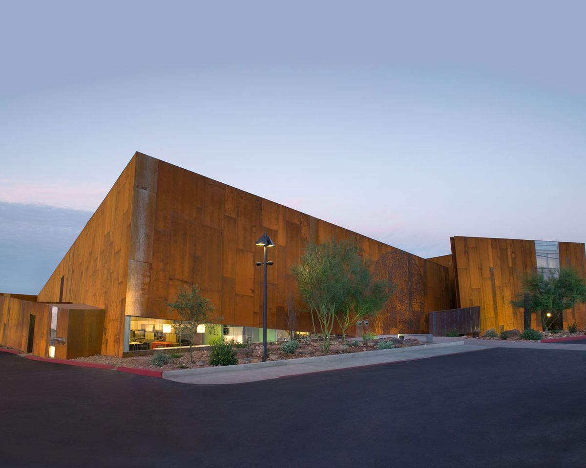 The exterior of the Arabian Library in Arizona. The facade is wooden and the roof is flat.