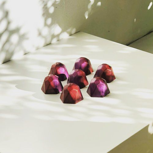 Seven hexagonal bonbons covered in purple and red airbrushed shimmers are arranged in a circle.
