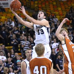 Utah State's Preston Medlin (13) shoots past Montana Tech's Brandon Rydberg (40) and Adam Greger, right, during the first half of an NCAA college basketball game in Logan, Tuesday, Feb. 14, 2012.