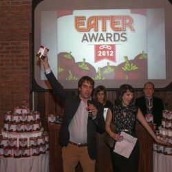 Eater founder Lock Steele and Editorial Director Amanda Kludt hold and point at Eater Awards tomato cans.