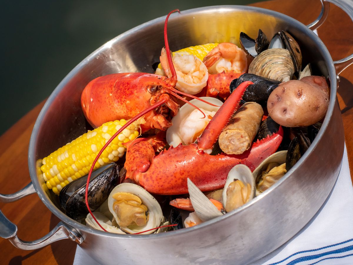 A high-walled, stainless steel pot is filled with lobster, shrimp, sausage, oysters, and clams