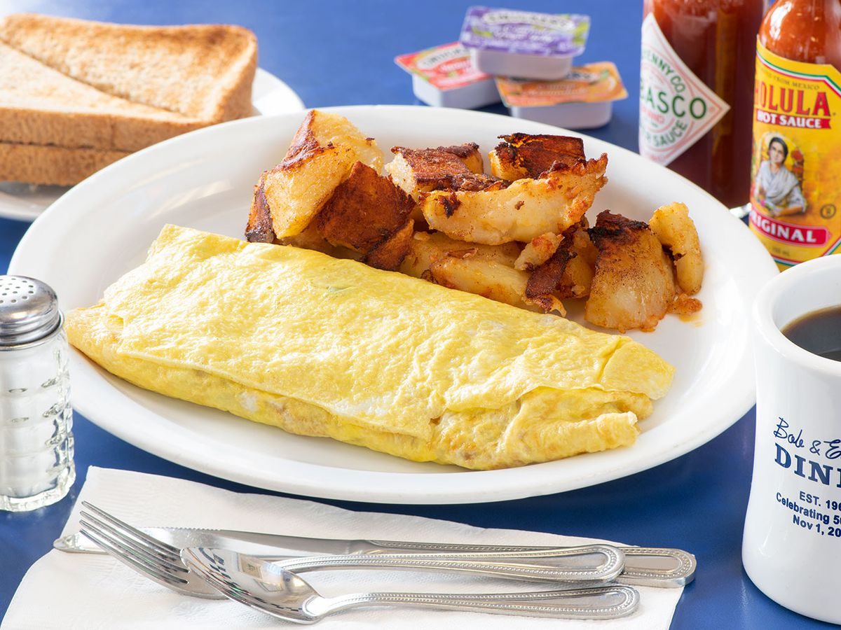 An omelet with home fries in the background, utensils in front, and coffee on the side.