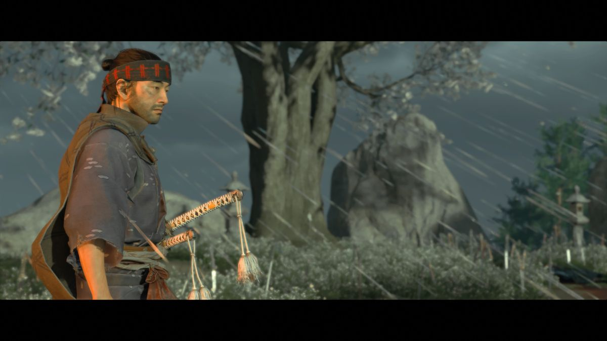 Ghost of Tsushima's main character stands in still in a windy rainstorm