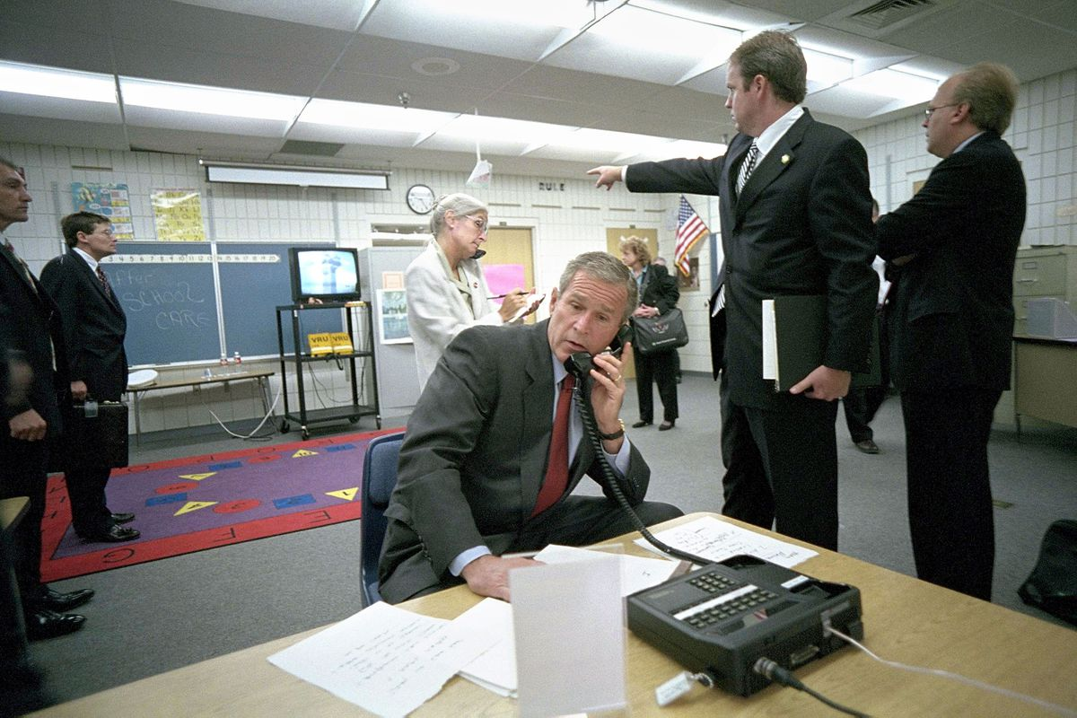 U.S. President George W. Bush (C) makes a telephone call as White House Director Of Communications Dan Bartlett points to video footage of the terrorist attack on the World Trade Center from Emma Booker Elementary School on September 11, 2001 in Sarasota, Florida.