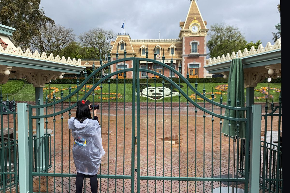 In this March 16, 2020, file photo, a visitor to Disneyland in Anaheim, Calif., takes a photo through a locked gate at the entrance. Disneyland has been shut down due to the novel coronavirus outbreak. If Gov. Gavin Newsom's so-called roadmap to ease coronavirus restrictions hinted at a return to a normal Californians could appreciate - a summer trip in the car - it quickly became apparent they wouldn't be leaving home soon.
