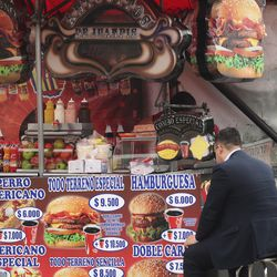 A man eats form a street stand in Bogota, Colombia, on Sunday, Aug. 25, 2019.