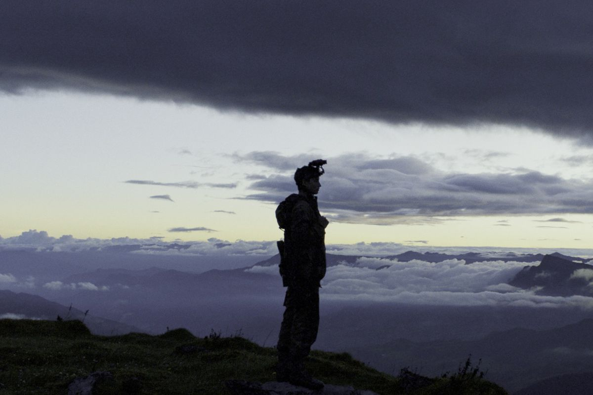 a boy stands atop a mountain in military gear, silhouetted by the setting sun