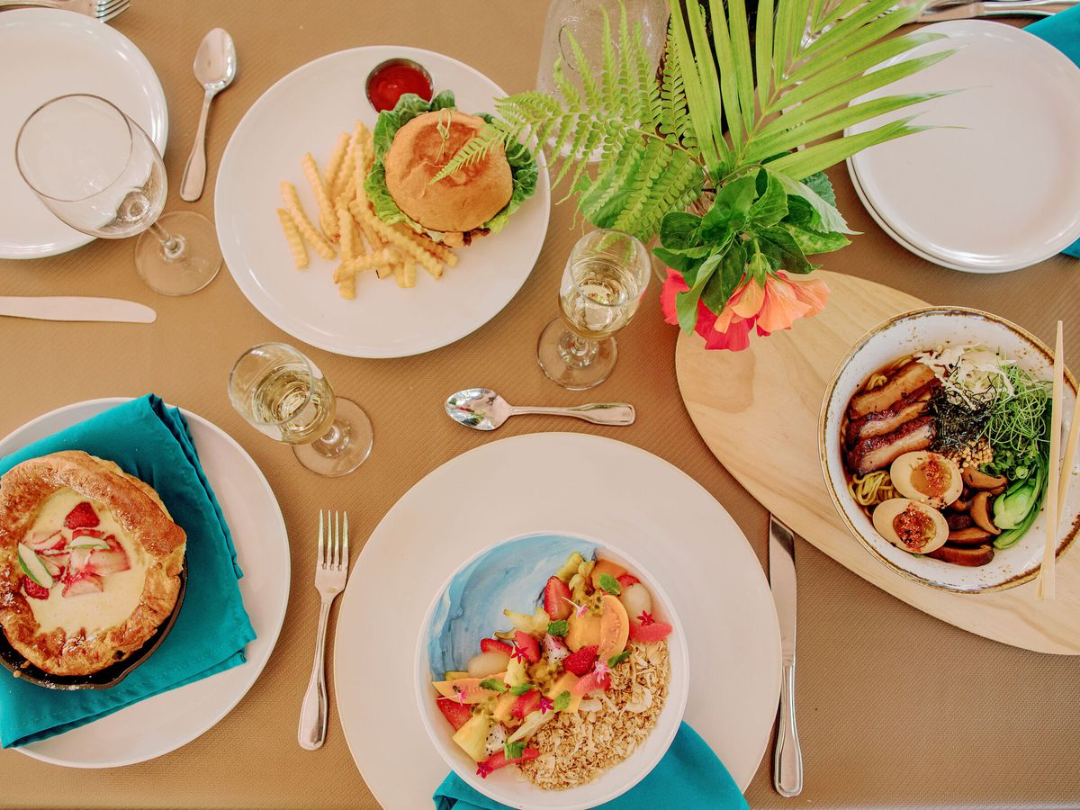 From above, a table laden with dishes like dutch baby pancake, a sandwich, a bowl of ramen, and a fruit bowl, with a bright plant for a centerpiece