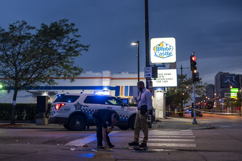Chicago police work the scene where three people were shot in the 3900 block of West Madison Street, in the East Garfield Park neighborhood, Monday, June 28, 2021.