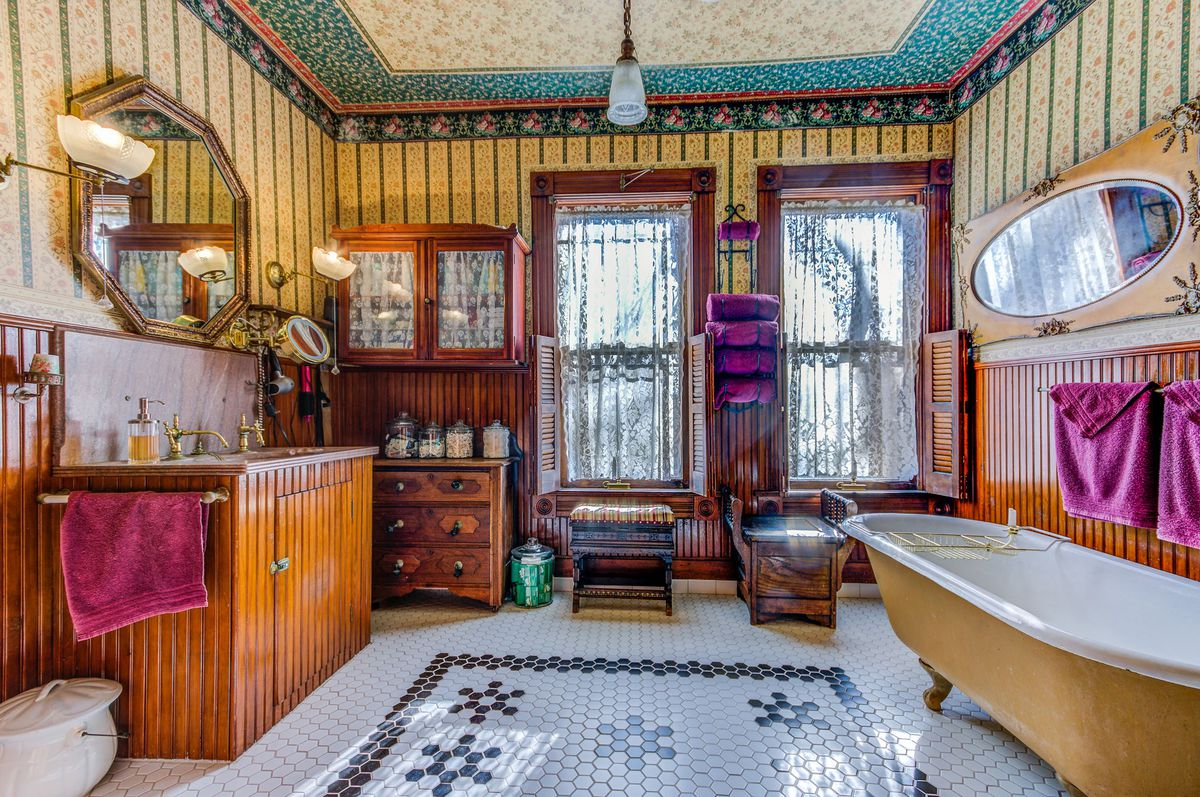 A bathroom features detailed tile, a clawfoot tub, and wooden cabinets.
