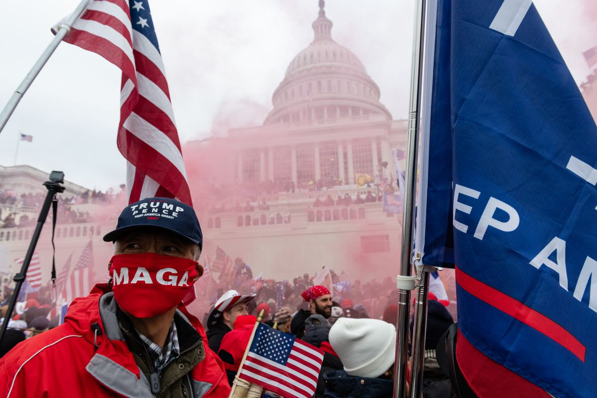A man in a blue Trump/Pence hat and red MAGA bandana stands amid red smoke, emitting from a smoke grenade, in front of the U.S. Capitol building in Washington, D.C. A mob of supporters of outgoing President Donald Trump breached the building on Jan. 6, 2021.