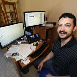 In this Wednesday, June 14, 2017, photograph, Danny Aguilar poses from his office in his home in Lakewood, Colo. Aguilar, like nearly half of Americans surveyed in a new poll conducted by The Associated Press-NORC Center Public Affairs Research, said they will not be taking a vacation this summer because they can not afford it or can not get time away from the job.