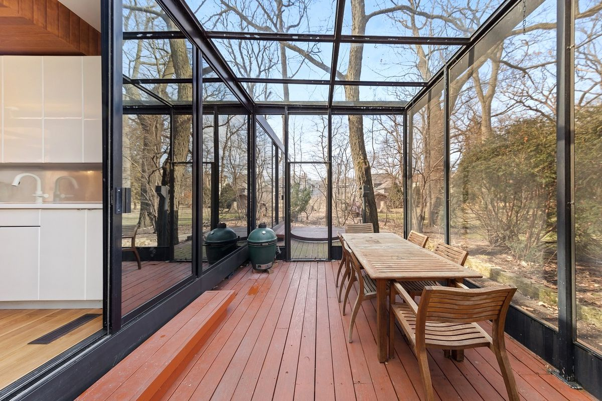 A sun porch with glass walls and ceiling. There's red wood decking and wooden chairs around a table and a grill.
