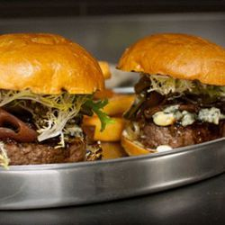 Chef McBride's Blue Duck Tavern bar burger is made like a jelly roll — beef is stuffed with short rib scraps and duck confit, topped with a roasted red onion, house-made pickles and Worcestershire, bleu cheese, pickled green tomato and a brioche bun.