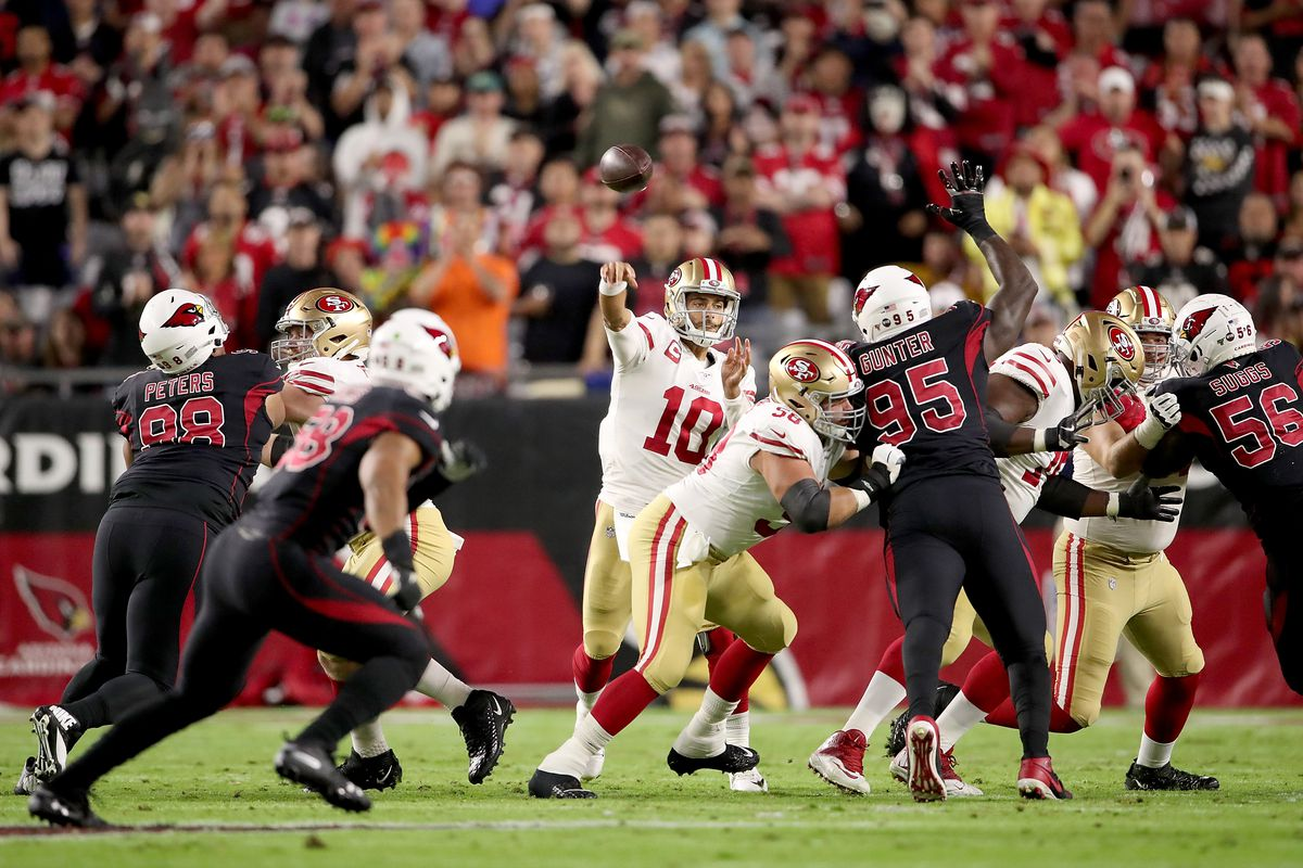 Quarterback Jimmy Garoppolo of the San Francisco 49ers delivers a pass over the defense of the Arizona Cardinals during the game at State Farm Stadium on October 31, 2019 in Glendale, Arizona.