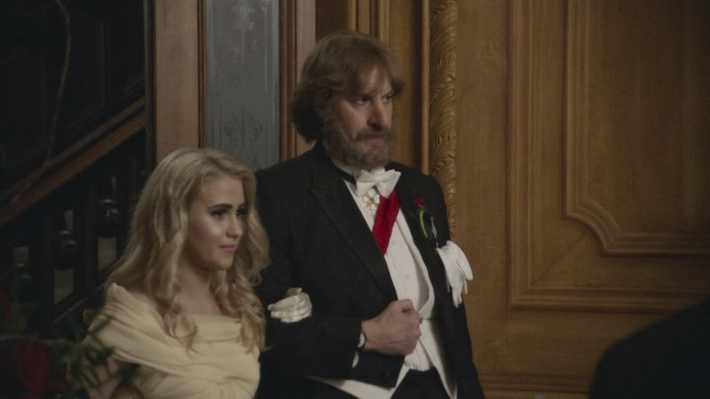 A woman and a man in formal clothing enter a ballroom, arm in arm.
