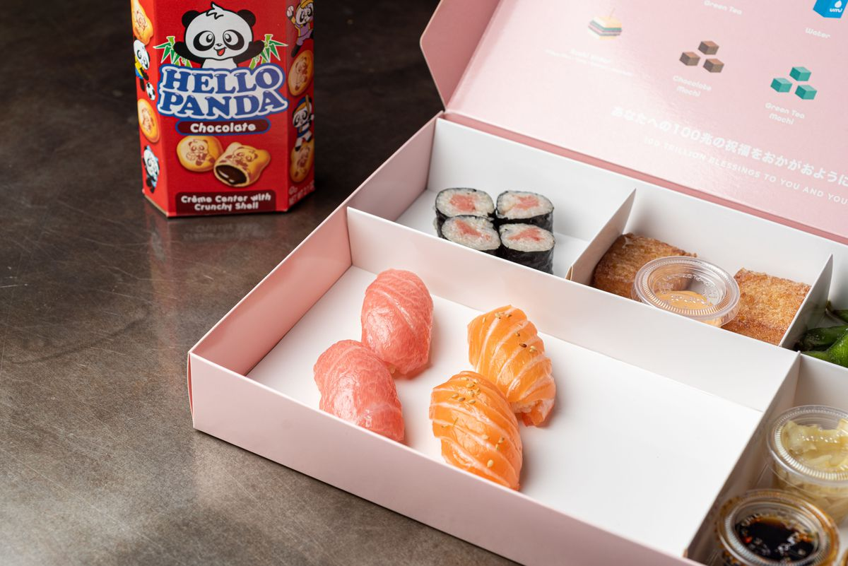 Four pieces of sushi inside of a pink box, with snacks behind in a dark room.