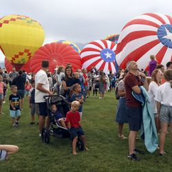 Crowds gather to watch hot air balloons inflate during Balloon Fest on Bulldog Field in Provo on Friday, July 2, 2021. The balloons could not fly due to weather but were inflated for display.