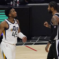 Los Angeles Clippers guard Paul George, right, celebrates during a timeout as Utah Jazz guard Donovan Mitchell walks by during the second half in Game 6 of a second-round NBA basketball playoff series Friday, June 18, 2021, in Los Angeles.