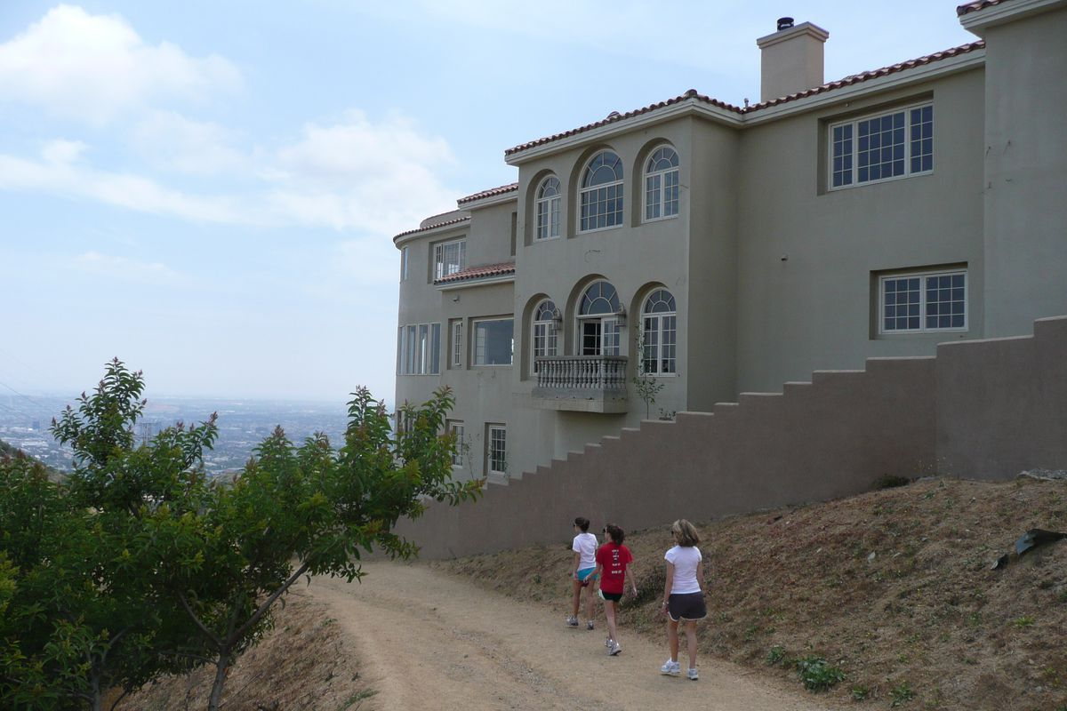 Hikers walk next to huge pink house