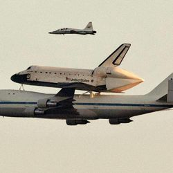 Space shuttle Endeavour sits atop the shuttle aircraft carrier, passes above the Austin, Texas, skyline Thursday, Sept. 20, 2012.   Endeavour is making a final trek across the country to the California Science Center in Los Angeles, where it will be permanently displayed.
