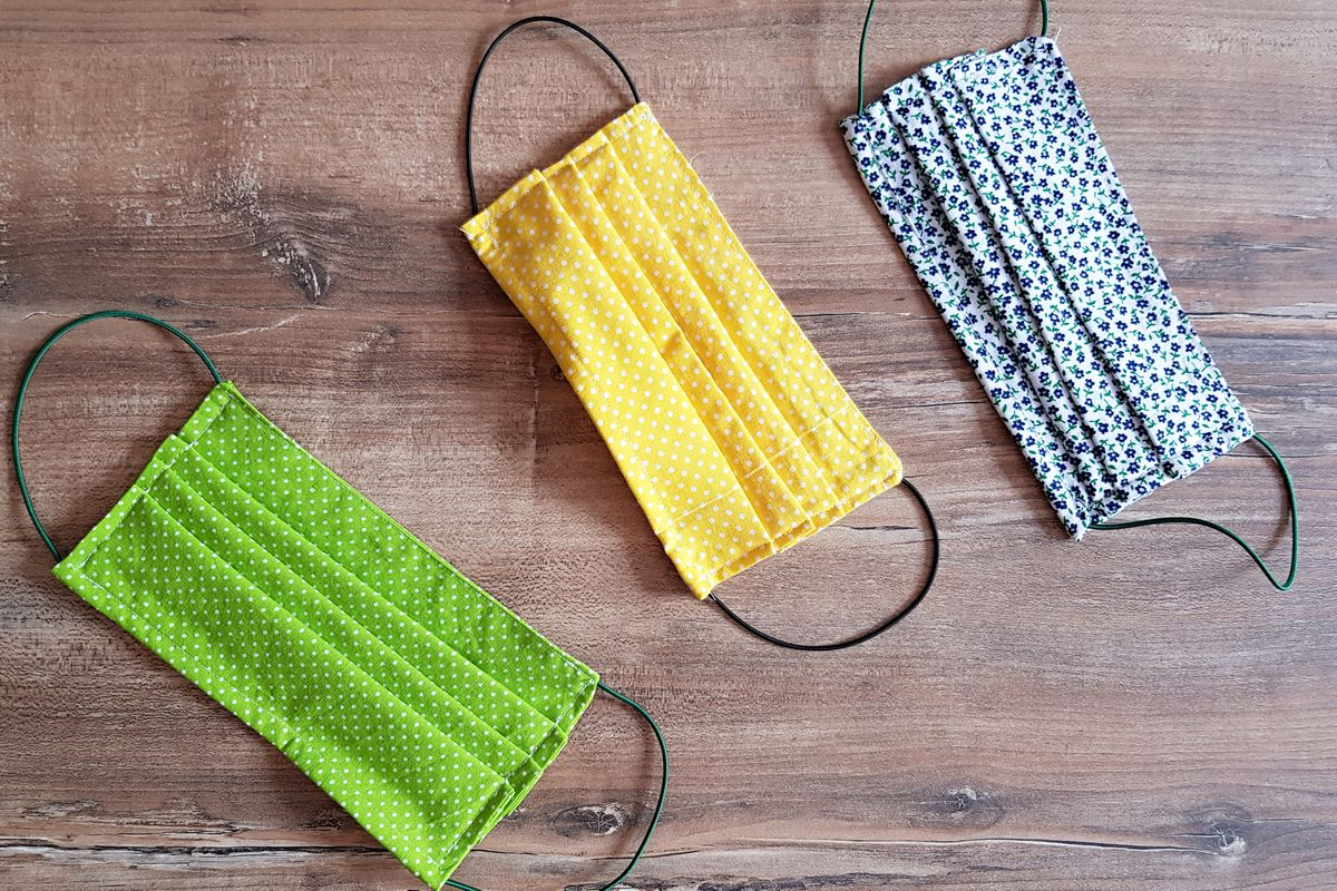 Three cloth face masks lying on a table, in green yellow, and blue