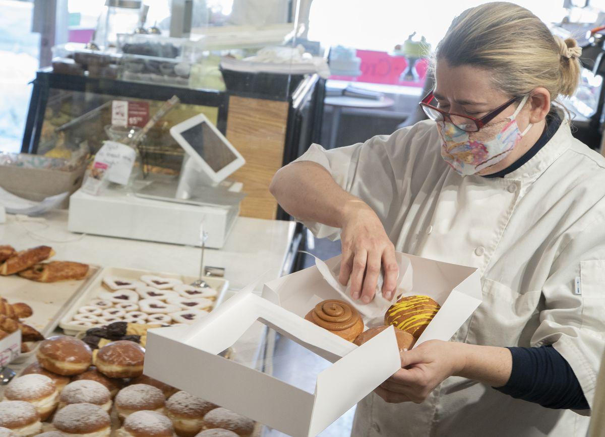 A woman in a mask places different types of paczki in a white bakery box.
