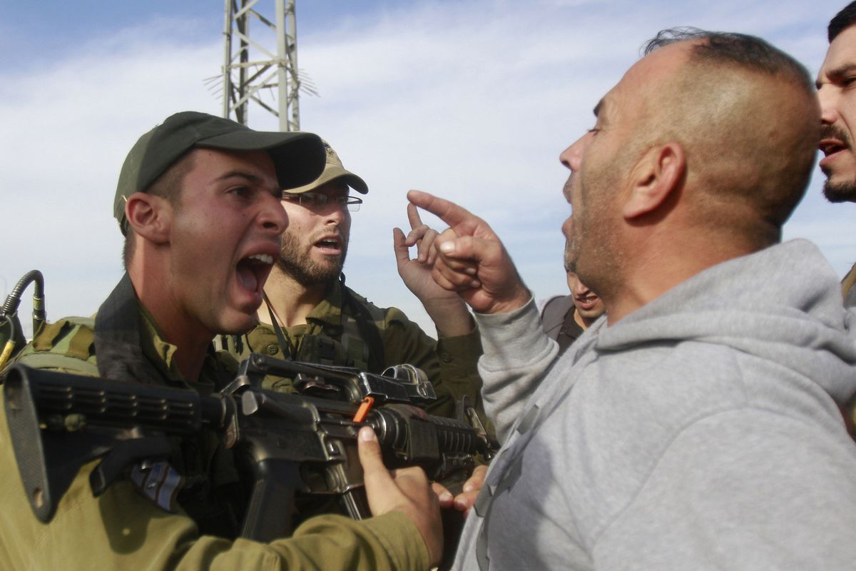 An Israeli soldier argues with a Palestinian demonstrator.
