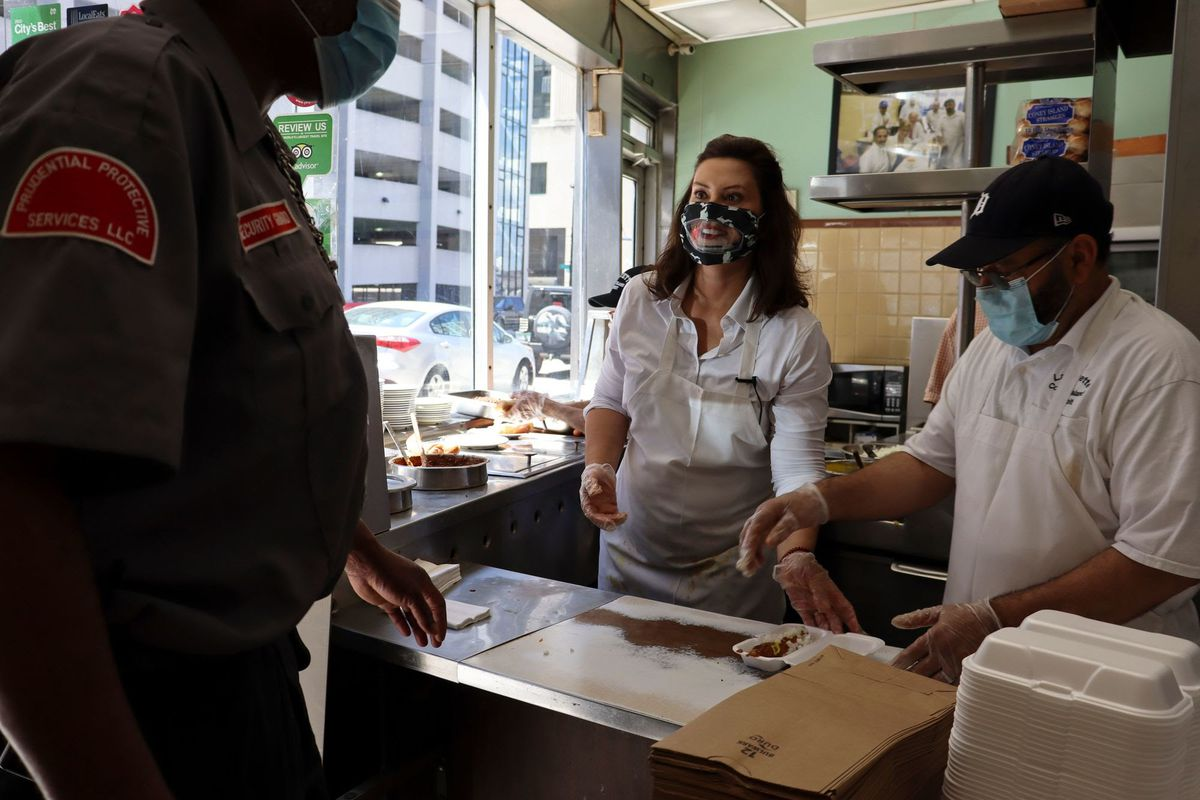 Gov.Whitmer speaks to a security guard while standing next to a masked and gloved employee at the Lafayette Coney Island counter.