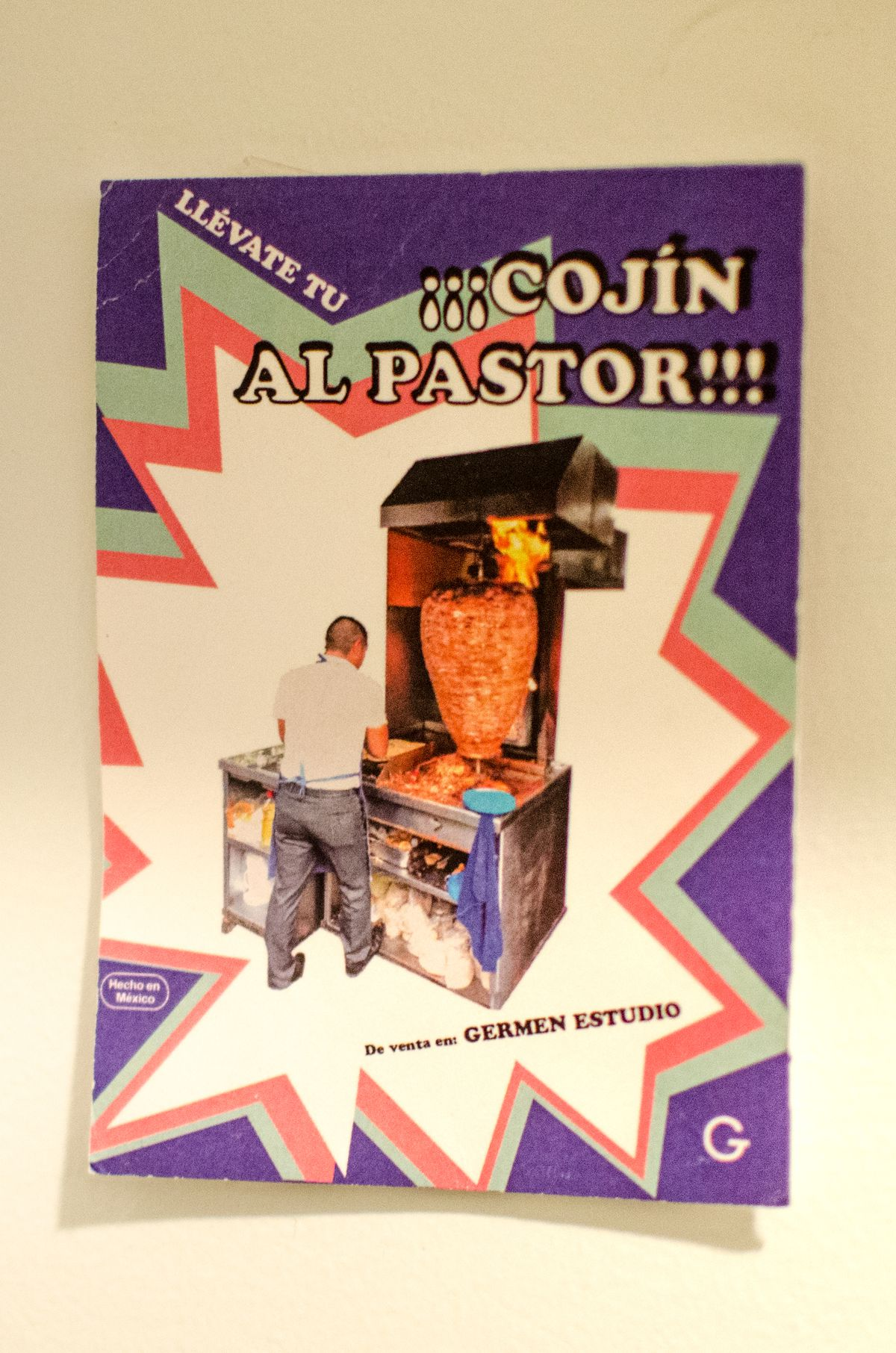 """A piece of paper features a photo of a man cooking al pastor and the words """"Llevate tu"""" and """"Cojin al pastor"""""""