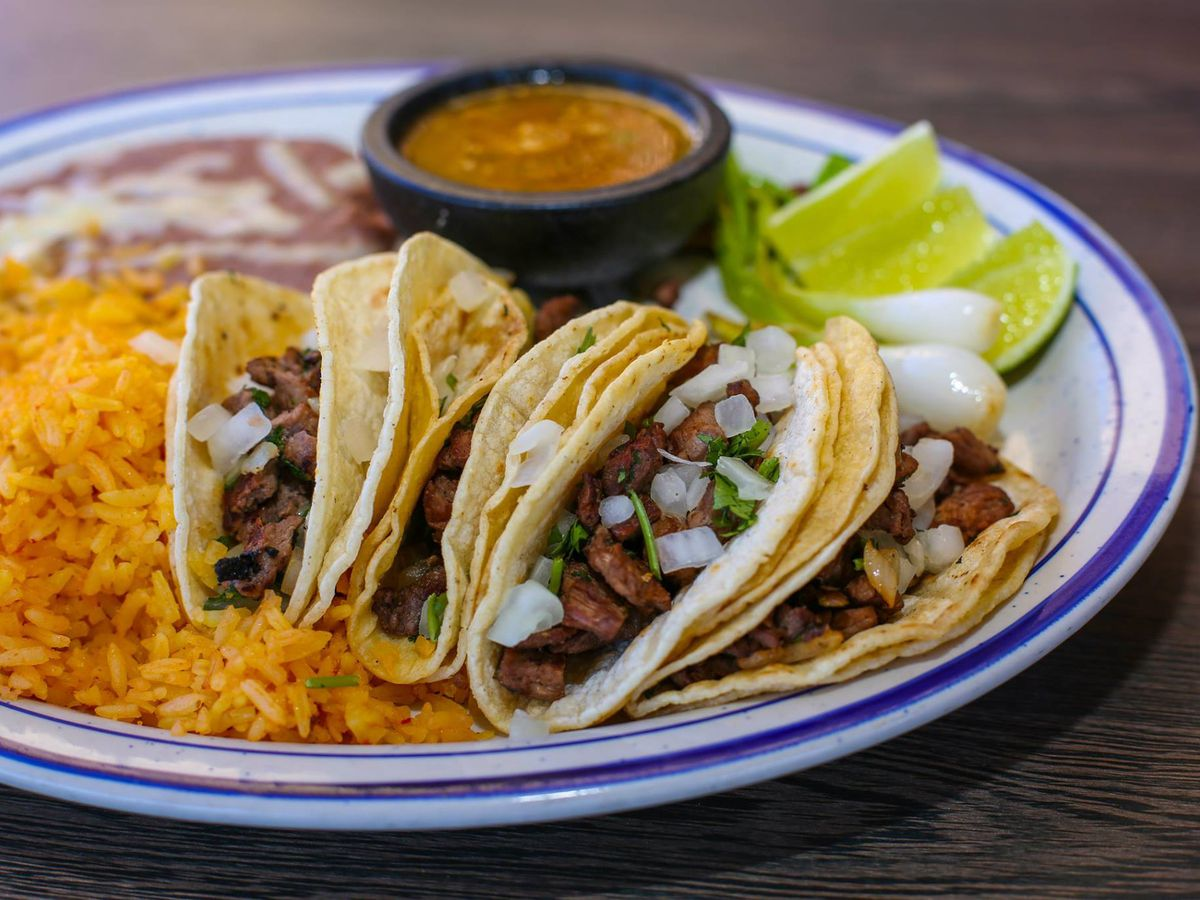 An oval plate of four street tacos with rice