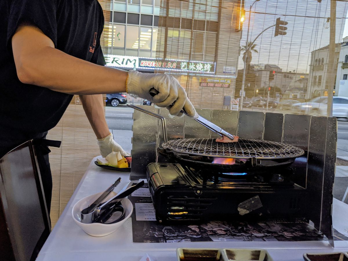 A gloved hand reaches toward a grill-top pan on a stove with tongs holding food.